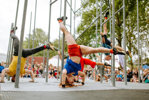 Dancers in bright clothing doing handstands among metal scaffolding