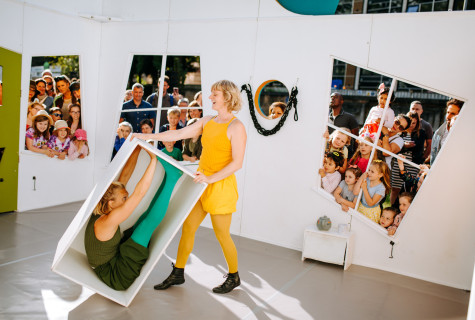 In the centre of a white house-shaped stage, a woman dressed all in yellow moves a box containing a woman dressed all in green. The audience watch on through the windows.