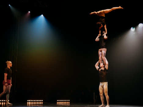 Three performers are balanced on top of one another: the performer at the top is upside down, doing the splits. Another performer looks on.