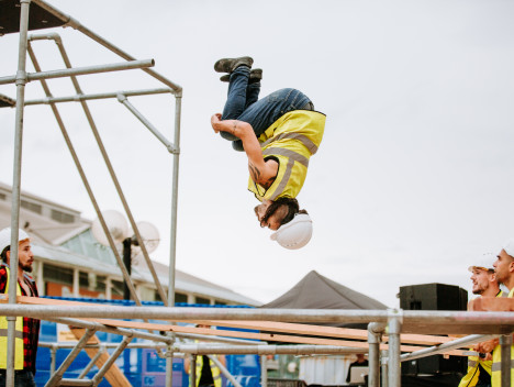 A performer in a white hard hat and yellow reflective jacket is upside down, mid-air, among metal scaffolding.
