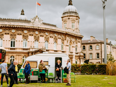 A caravan on grass with participants of Grief Series in the foreground and Hull Maritime Museum in the background