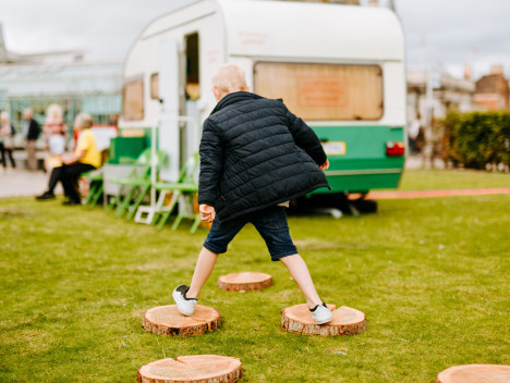 A child using circles of bark as stepping stones. The Grief Series caravan installation is in the background.