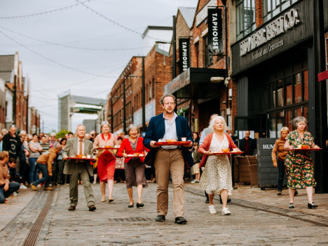 Six older performers carrying dinner trays along Humber Street, in a performance of The Great Escape by Adhok.