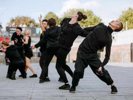 Seven dancers dressed all in black perform.