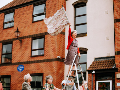 An older performer standing at the top of a ladder waves a floral flag in a performance of The Great Escape by Adhok.