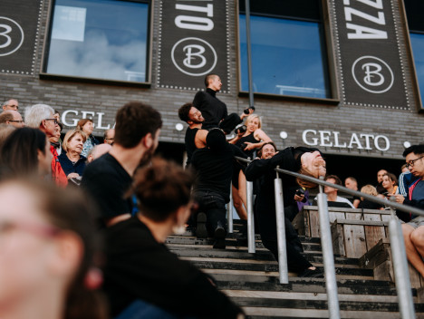 A group of dancers dressed all in black perform in the aisle between an audience sat in an outdoor amphitheater.