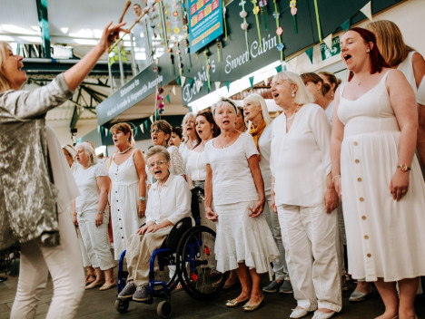 Hull's Freedom choir, dressed all in white, perform in Trinity Market..