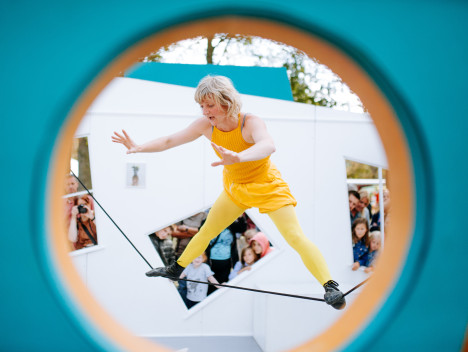 A performer dressed all in yellow balances on a tightrope. This is viewed through a circular window.