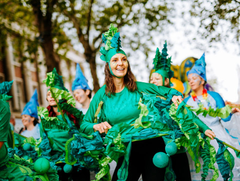 Performers in green costumes take part in the Hull International Carnival parade.
