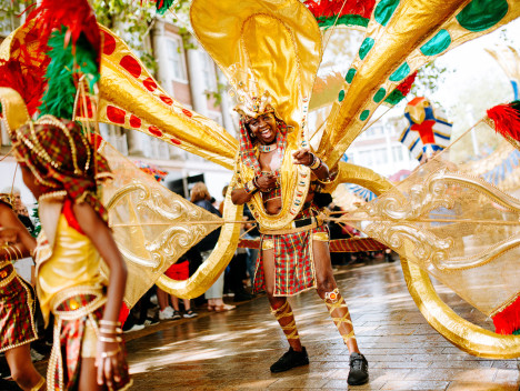 A performer in a large and ornate red and gold costume takes part in the Hull International Carnival parade.