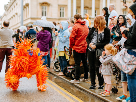A performer in a spiky orange suit entertains the crowd.