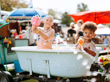 Two children with water pistols and a flamingo-shaped watering can play in a bathtub.