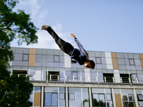 A performer in a tracksuit is upside down at a diagonal angle in the air.