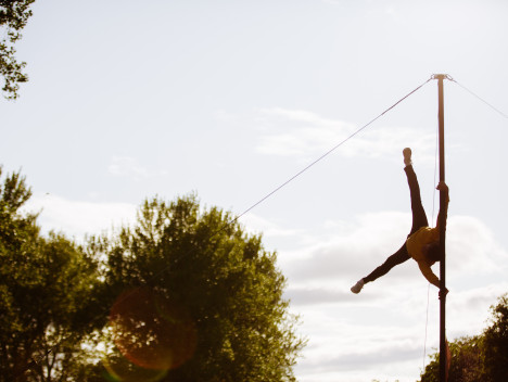 A performer does the splits whilst suspended in the air.