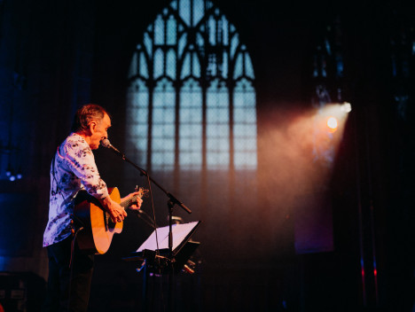 A man, playing an acoustic guitar, sings into a microphone. A large church window is in the background.