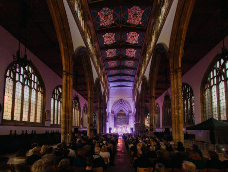 The audience seated in Hull Minster. Purple light illuminates the front of the church.
