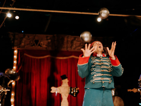 A performer in a green and red outfit juggles silver balls.